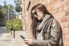Ragazza che manda un sms sul suo telefono cellulare con la parete urbana sopra Fotografie Stock