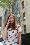Ragazza che manda un sms sulla seduta dello Smart Phone Fotografia Stock Libera da Diritti