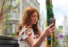 Ragazza che manda un sms sulla seduta dello Smart Phone Immagini Stock Libere da Diritti