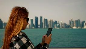 Ragazza che manda un sms sullo smartphone con i grattacieli nel fondo stock footage