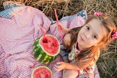 Ragazza che mangia anguria Bambino felice nel campo Umore di estate fotografia stock