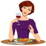 Ragazza che mangia bistecca di color salmone e che beve vino rosso Fotografia Stock