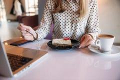 Ragazza che mangia dolce in un caffè Bionda in camicia del pois con il computer portatile fotografia stock libera da diritti