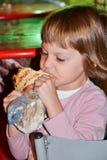 Ragazza che mangia hamburger sulla via Immagini Stock