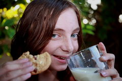 Ragazza che mangia i biscotti e latte fotografie stock libere da diritti