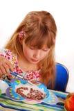 Ragazza che mangia i fiocchi di granturco del cioccolato Fotografia Stock
