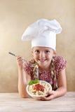 Ragazza che mangia pasta con la salsa ed il basilico di pomodori Fotografie Stock