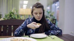 Ragazza che mangia pizza ad un caffè Un adolescente in pizzeria sta avendo cena stock footage