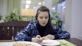 Ragazza che mangia pizza ad un caffè Un adolescente in pizzeria sta avendo cena video d archivio