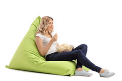 Ragazza che mangia popcorn messo sul beanbag Immagine Stock