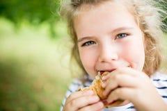 Ragazza che mangia spuntino al parco di estate Immagini Stock Libere da Diritti