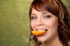 Ragazza che mangia un arancio Immagine Stock
