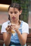 Ragazza che mangia un dolce di cioccolato con crema inglese Fotografie Stock Libere da Diritti