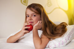 Ragazza che mangia una mela a letto Fotografia Stock