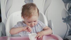 Ragazza che mangia yogurt sulla cucina, piccolo alimento del bambino del bambino, bambino che mangia con il cucchiaio video d archivio