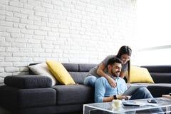 Ragazza che massaggia ragazzo su Sofa At Home immagini stock libere da diritti