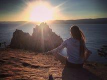 Ragazza che medita al tramonto su lago Baikal Immagine Stock Libera da Diritti