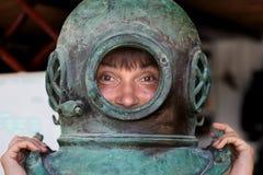 Ragazza che mette su un casco di immersione subacquea Fotografie Stock Libere da Diritti