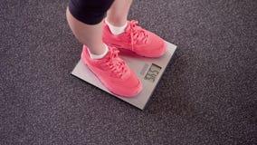 Ragazza che misura il suo peso sulle scale elettroniche Dimagrisca le gambe femminili in scarpe da tennis rosa su equilibrio digi archivi video