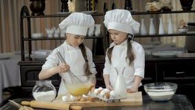 Ragazza che monta le uova in ciotola di vetro alla tavola di legno archivi video