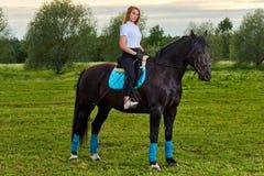 Ragazza che monta un cavallo attraverso paese fotografia stock libera da diritti