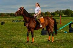 Ragazza che monta un cavallo attraverso paese fotografia stock