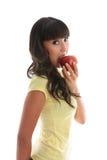 Ragazza che morde in una mela rossa immagine stock