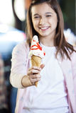 Ragazza che mostra il gelato saporito con lo sciroppo di fragole fotografia stock