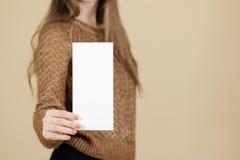 Ragazza che mostra il libretto bianco in bianco dell'opuscolo dell'aletta di filatoio Opuscolo presente Fotografie Stock Libere da Diritti
