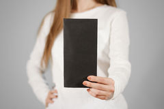 Ragazza che mostra il libretto nero in bianco dell'opuscolo dell'aletta di filatoio Opuscolo presente Fotografia Stock