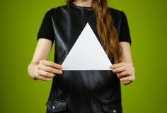 Ragazza che mostra il libretto triangolare bianco in bianco dell'opuscolo dell'aletta di filatoio Foglia Fotografia Stock