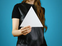 Ragazza che mostra il libretto triangolare bianco in bianco dell'opuscolo dell'aletta di filatoio Foglia Immagine Stock