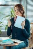 Ragazza che mostra un taccuino e un pollice in bianco su Fotografia Stock Libera da Diritti