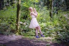 Ragazza che oscilla nella foresta Immagini Stock