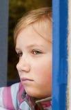 Ragazza che osserva attraverso la finestra Fotografie Stock