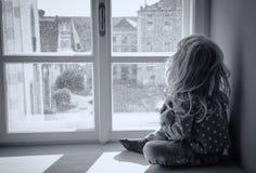 Ragazza che osserva attraverso la finestra Fotografia Stock
