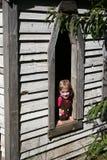 Ragazza che osserva fuori finestra Fotografia Stock