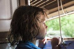 Ragazza che osserva fuori la finestra Fotografie Stock