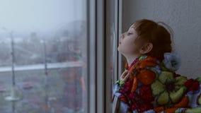 Ragazza che osserva fuori la finestra le precipitazioni nevose archivi video