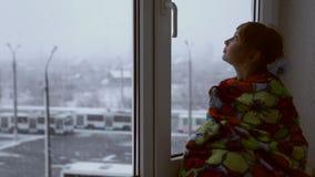 Ragazza che osserva fuori la finestra le precipitazioni nevose video d archivio