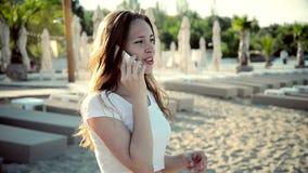 Ragazza che parla alla spiaggia del telefono cellulare nelle vacanze estive video d archivio
