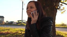 Ragazza che parla sul telefono in autunno nel parco al tramonto archivi video