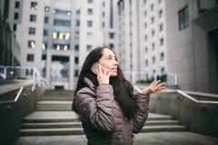 Ragazza che parla sul telefono cellulare nel centro di affari del cortile la ragazza con capelli scuri lunghi si è vestita in riv fotografia stock libera da diritti