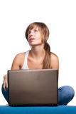 Ragazza che pensa con il computer portatile Fotografie Stock Libere da Diritti