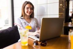 Ragazza che per mezzo del computer portatile e bevanda fresca al caffè Fotografia Stock