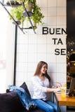 Ragazza che per mezzo del computer portatile e bevanda fresca al caffè Fotografia Stock Libera da Diritti