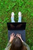 Ragazza che per mezzo del computer portatile fuori su erba Fotografia Stock Libera da Diritti