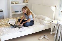 Ragazza che per mezzo del computer portatile per il compito che si siede fornito di gambe trasversale sul letto Immagine Stock
