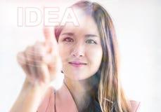 Ragazza che per mezzo del dito per toccare l'IDEA nella parte anteriore Immagini Stock Libere da Diritti