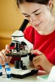 Ragazza che per mezzo del microscopio Fotografia Stock Libera da Diritti